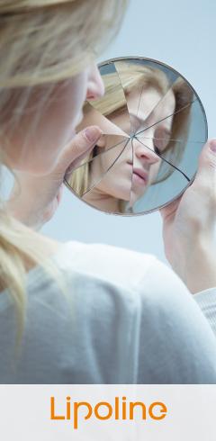 Kobieta przegląda się w pękniętym lusterku